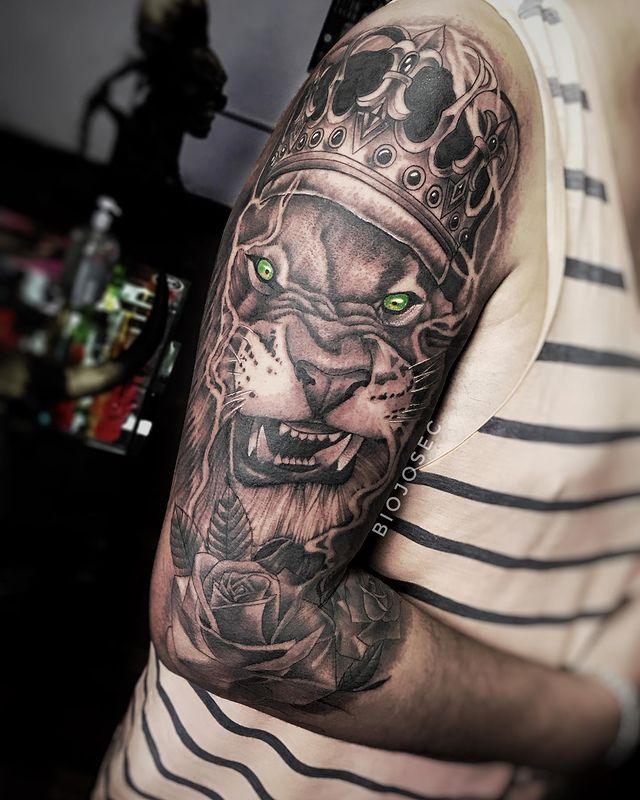 Green Eyed Lion with Crown Tattoo